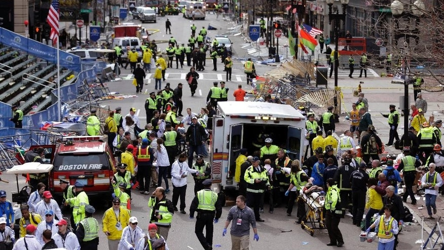 FILE - In this April 15, 2013, file photo, medical workers aid injured people following an explosion at the finish line of the 2013 Boston Marathon in Boston. Dzhokhar Tsarnaev was convicted Wednesday, April 8, 2015, in federal court in Boston on multiple charges in the bombings. Three people were killed and more than 260 were injured when twin pressure-cooker bombs exploded near the finish line. (AP Photo/Charles Krupa, File)