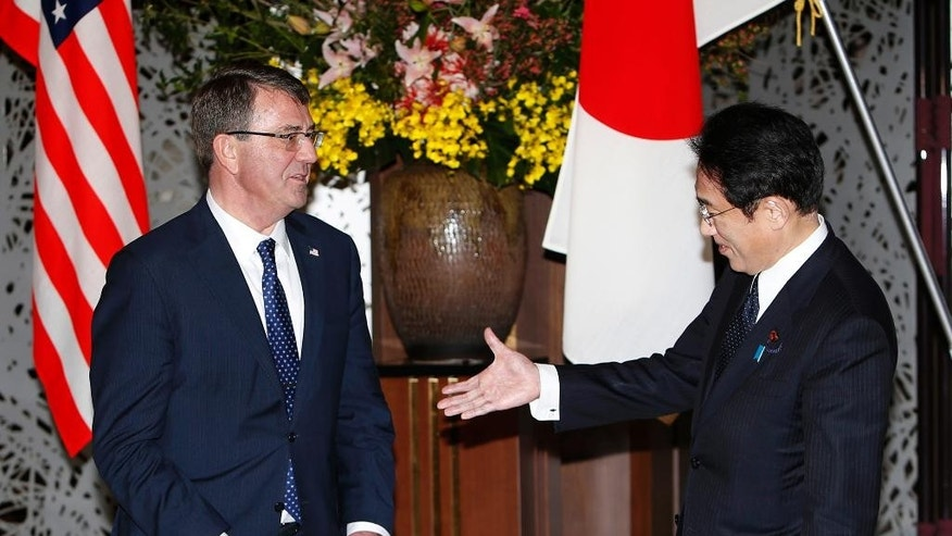 Japanese Foreign Minister Fumio Kishida, right, prepares to shake hands with  U.S. Defense Secretary Ash Carter before their working lunch at the foreign ministry's Iikura guest house in Tokyo Wednesday, April 8, 2015. (AP Photo/Yuya Shino, Pool)