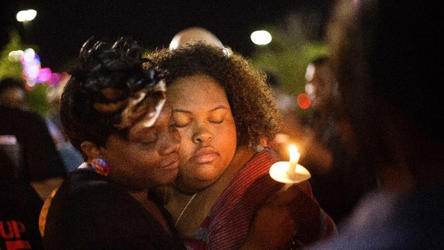 Chasyn Carter, right, of North Charleston, S.C., embraces Candice Ancrum, of Summerville, S.C., during a candlelight vigil outside city hall protesting the shooting death of Walter Lamer Scott, Wednesday, April 8, 2015, in North Charleston, S.C. Scott was killed by a North Charleston police office after a traffic stop on Saturday. The officer, Michael Thomas Slager, has been fired and charged with murder. (AP Photo/David Goldman)