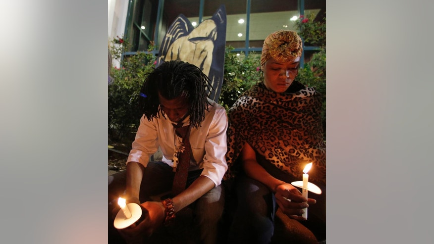 Protestors hold candles in remembrance of Walter Scott during a protest in front of city hall in North Charleston, S.C., Wednesday, April 8, 2015. Scott was killed by a North Charleston police officer after a traffic stop on Saturday. The officer, Michael Thomas Slager, has been charged with murder. (AP Photo/Chuck Burton)