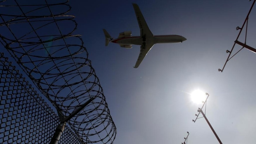 In this Friday, Feb. 6, 2015 photo, a passenger jet flies over the perimeter fence at the Los Angeles International Airport as it lands. Several hundred times from 2004 to 2015, intruders have hopped fences, slipped past guardhouses, crashed their cars through gates or otherwise breached perimeter barriers at more than two dozen of the busiest U.S. airports - sometimes even managing to climb aboard jets. (AP Photo/Chris Carlson)