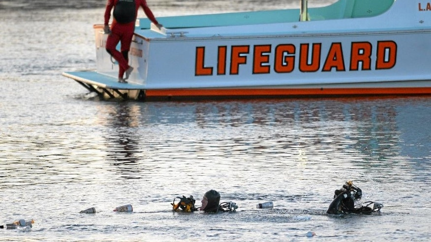 Divers emerge from the water as debris believed to be from the car floats to the surface where a car went off the berth and into the water at the San Pedro Slip, in San Pedro, Calif., Thursday, April 9, 2015. The two children pulled from the submerged vehicle were hospitalized in grave condition, authorities said. (AP Photo/The Daily Breeze, Steve McCrank)