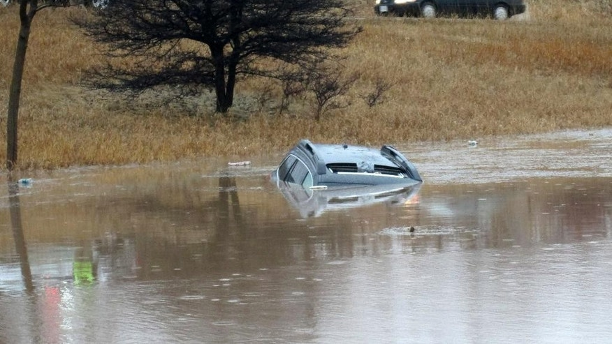 In this Thursday, April 9, 2015 photo provided by the Ozaukee County, Wisconsin, Sheriff's Office are vehicles that became partially submerged in flood water due to heavy rain in Port Washigton, Wisconsin. Official said no one was hurt and the road was closed. (Ozaukee County Sheriff's Office via AP)