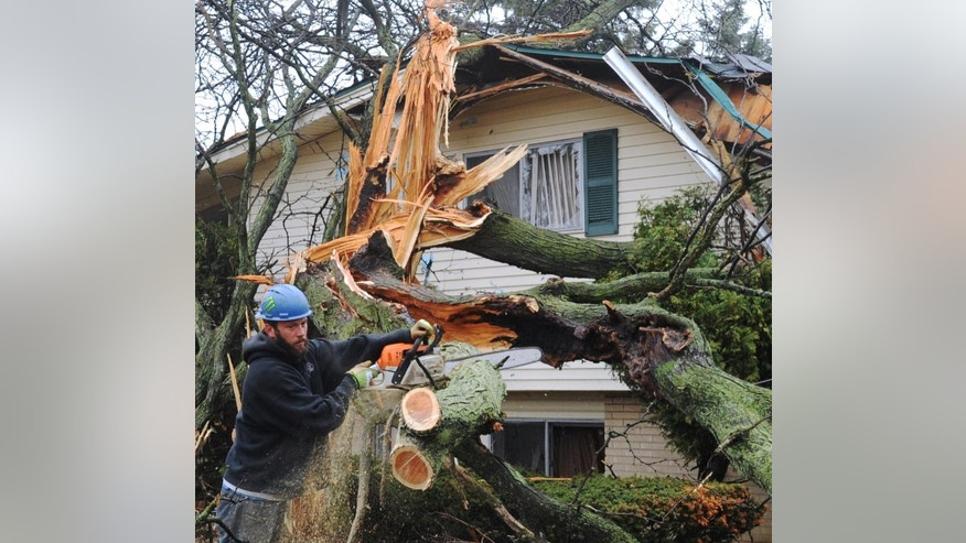 Bobby Buskell , center, and a crew from All State Tree Service Inc. clean up damage from a lighting strike of a home in Southfield, Mich.,  on Thursday, April 9, 2015.  The National Weather Service says severe thunderstorms are possible into early Friday, packing damaging wind gusts, heavy downpours and hail. (AP Photo/Detroit News, Brandy Baker)  DETROIT FREE PRESS OUT; HUFFINGTON POST OUT