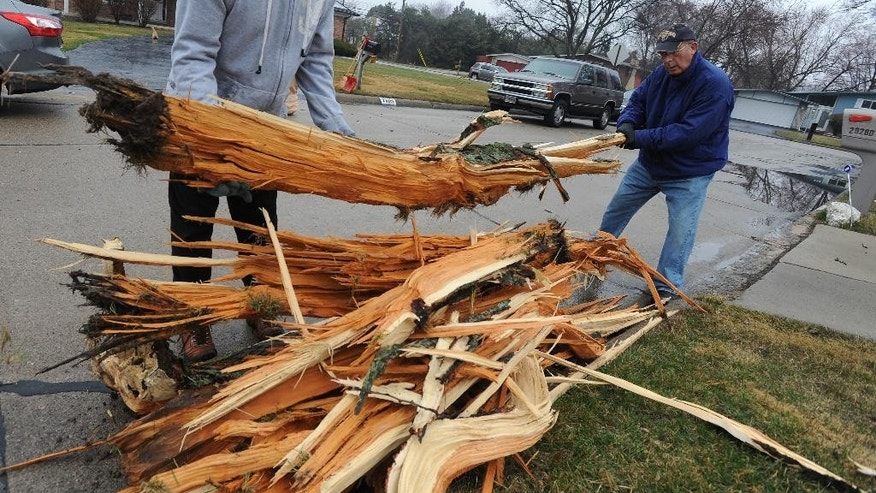Neighbors Robert Frye, left, and Barry Winkler help clean up splintered tree parts that blasted into their yards after a storm passed the area in Southfield, Mich.,  on Thursday, April 9, 2015.  The National Weather Service says severe thunderstorms are possible into early Friday, packing damaging wind gusts, heavy downpours and hail. (AP Photo/Detroit News, Brandy Baker)  DETROIT FREE PRESS OUT; HUFFINGTON POST OUT