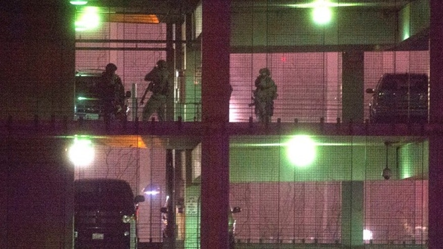 April 9, 2015: Police search a parking garage on the U.S. Census  Bureau headquarters campus for an armed man who, according to a fire official, shot a security guard at a gate to the facility in Suitland, Md. (AP Photo/Cliff Owen)
