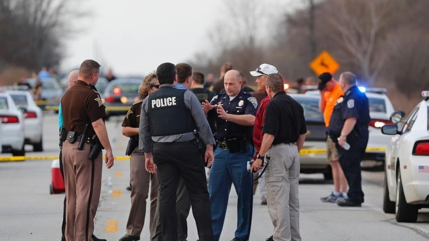 Law enforcement officers from several counties gather at the scene following a chase Thursday, April 9, 2015, near Monon, Ind. An armed robbery and car-jacking in Illinois turned into a two-state, multi-county pursuit. (AP Photo/Journal & Courier, John Terhune)