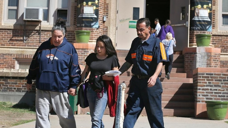 Cynthia and Sal Gonzales escort their daughter Rita away from Skinner Middle School, where three juveniles, two with guns, the other with a smoke device, were arrested, in Denver, Friday, April 10, 2015. No one was injured, and the school was on lockdown for about an hour, police said. (AP Photo/Brennan Linsley)