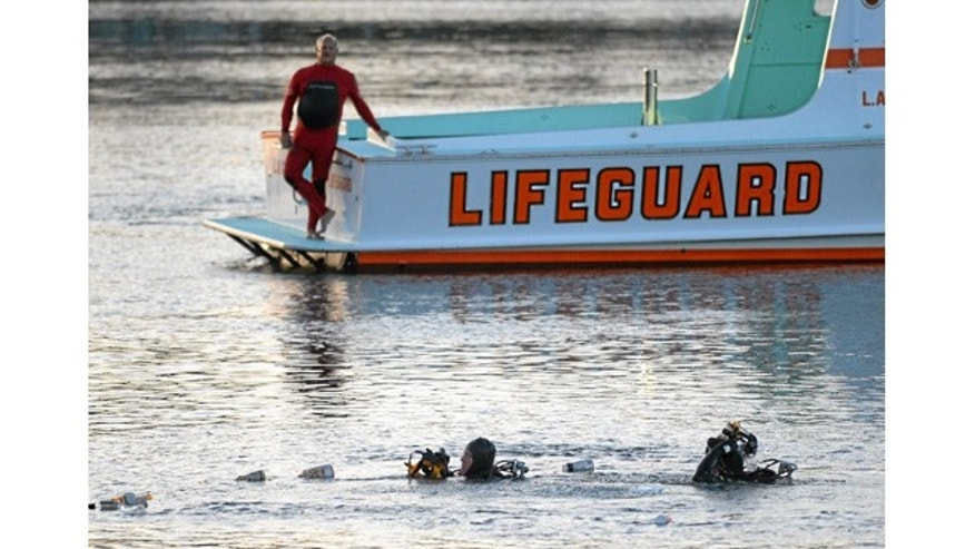 April 9, 2015: Divers emerge from the water in Los Angeles Harbor after two children pulled from submerged vehicle. (AP Photo/The Daily Breeze, Steve McCrank)