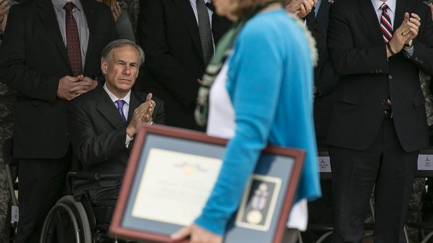 Joleen Cahill, foreground, wife of Michael Cahill who was killed during the attack by Maj. Nidal Hasan in the 2009 Fort Hood shooting, carries her husband's Defense of Freedom Medal back to her chair, as Texas Gov. Greg Abbott, lower left, and Sen. Ted Cruz, right, applaud the family members of those killed in the shooting during a ceremony held at Fort Hood, Texas, Friday, April 10, 2015.  Survivors and family members of those killed during the attack were awarded medals: a Purple Heart for soldiers and Defense of Freedom Medals for civilians. (AP Photo/Austin American-Statesman, Rodolfo Gonzalez, Pool)