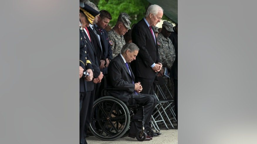 Texas Gov. Greg Abbott, seated, and Sen. John Cornyn, right, bow their heads during the invocation of a Purple Heart ceremony held at Fort Hood, Texas, Friday, April 10, 2015. Survivors and family members of those killed during the attack by Maj. Nidal Hasan in the 2009 Fort Hood shooting were awarded medals: the Purple Heart for soldiers and Defense of Freedom Medals for civilians.  (AP Photo/Austin American-Statesman, Rodolfo Gonzalez, Pool)