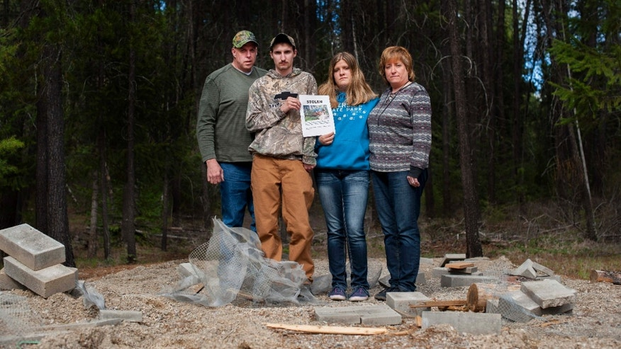 April 8, 2015: Moose Hempel, left, stands with his children, Tyler and Kayla and wife Chris, at the site where their cabin used to stand.