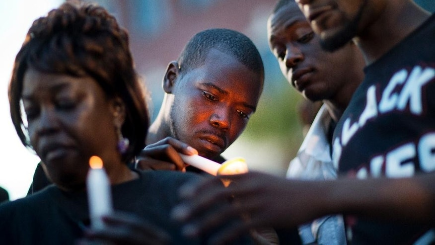 Diontre Moore, of North Charleston, S.C., center, lights a candle during a rally in North Charleston, S.C. on Friday, April 10, 2015 protesting the fatal police shooting of Walter Scott. Scott was killed by a police officer after a traffic stop on Saturday. Officer Michael Slager has been fired and charged with murder. (AP Photo/David Goldman)