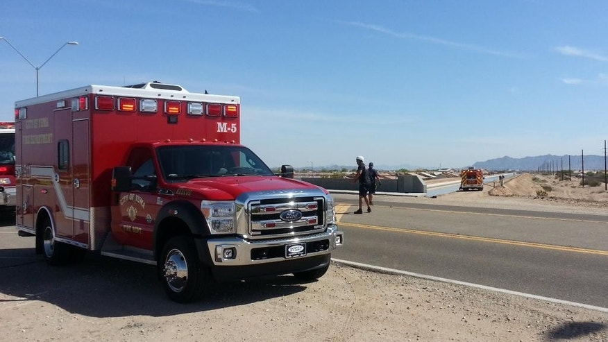 In this photo provided by Yuma Fire Department, authorities work a perimeter near a canal in Yuma, Ariz., Saturday, April 11, 2015. Twin 18-month-old boys were pronounced dead at a hospital after being pulled from the Arizona canal, police said Saturday. (AP Photo/Yuma Fire Department via Public Affairs for Yuma County, Kevin Tunell)