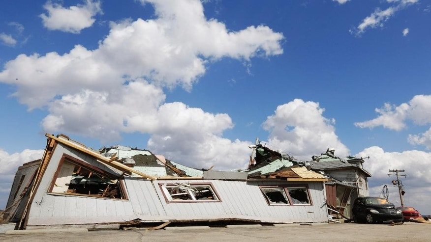 This photo shows Grubsteakers restaurant in Rochelle, Ill., Friday, April 10, 2015, after it was destroyed by severe weather that passed through the area Thursday night. Twelve people were trapped in the basement of the restaurant that collapsed. (AP Photo/Teresa Crawford)