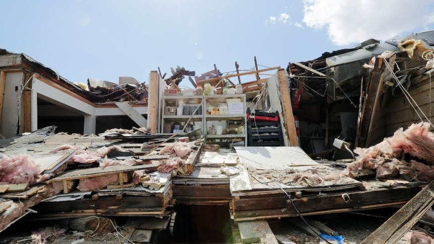 This photo shows the back of Grubsteakers restaurant in Rochelle, Ill., Friday, April 10, 2015, after it was destroyed by severe weather that passed through the area Thursday night. Twelve people were trapped in the basement of the restaurant that collapsed. (AP Photo/Teresa Crawford)