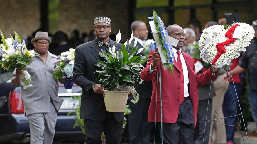 April 11, 2015: Men carry flowers into the World Outreach Revival Deliverance Ministries Christian Center before the funeral service in Summerville, S.C.,