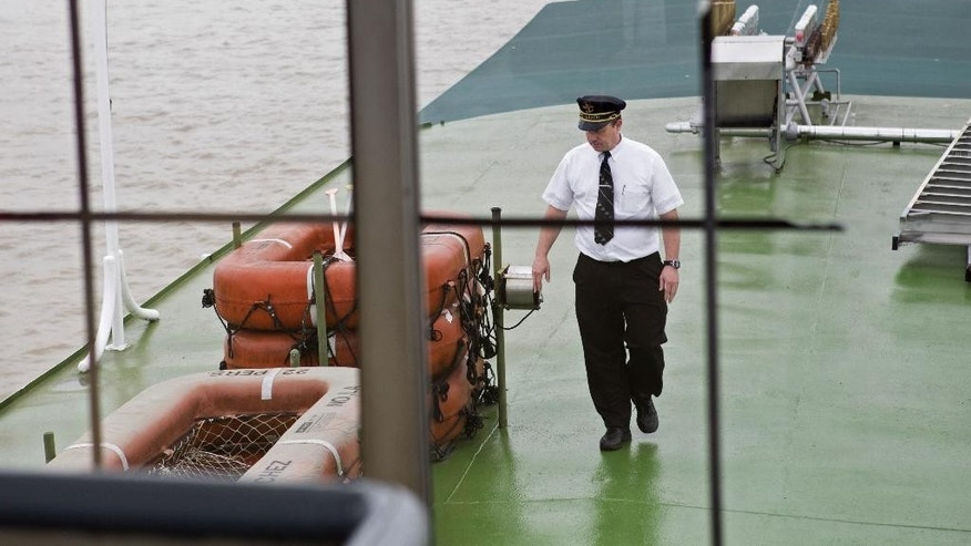 In a Sunday, March 15, 2015 photo, Captain Donald Houghton walks on the deck of the Natchez steamboat on the Mississippi River in New Orleans. The Natchez, which celebrates its 40th anniversary on Monday, April 13, is only one of three steam-powered boats left in the Mississippi River valley.  (AP Photo/Samantha Kaplan)