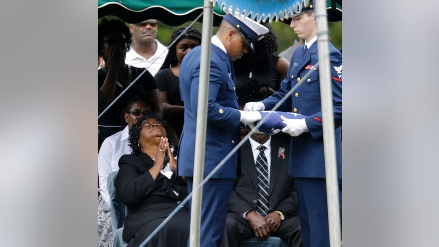 Judy Scott, left, looks up as an honor guard folds a U.S. flag that covered the casket of her son, Walter Scott, before it's presented to her during his burial service in Charleston, S.C. on Saturday, April 11, 2015. Walter Scott was fatally shot by a North Charleston, S.C., police officer a week earlier after a traffic stop. Officer Michael Slager has been charged with murder. (AP Photo/David Goldman)