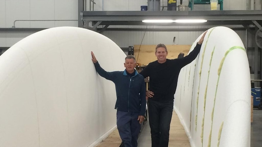 In this undated photo provided by Cumulus Media, Project Manager Bob Steel, left, and President of mouldCAM John Barnitt, right, stand between two halves of a surfboard, near Providence, R.I. The engineering technology and manufacturing company, mouldCAM, has set out to build the world's largest surfboard. WPRO-AM reports Bristol-based mouldCAM is building the board for the Visit Huntington Beach campaign in California, which hopes to break the world record for the most people to catch a wave on a surfboard. (Andrew Augustus/Cumulus Media via AP)