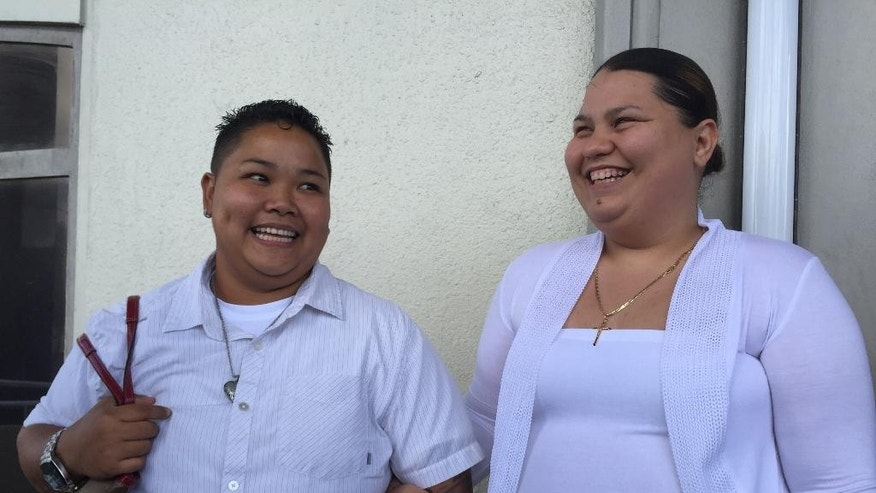 Loretta M. Pangelinan, left, and Kathleen M. Aguero smile after filing motions in front of the U.S. Federal Court in Hagatna in Guam Monday, April 13, 2015. The couple is seeking the federal court order to compel the Government of Guam Department of Public Health and Social Services to accept their marriage license application. (AP Photo/Grace Garces Bordallo)