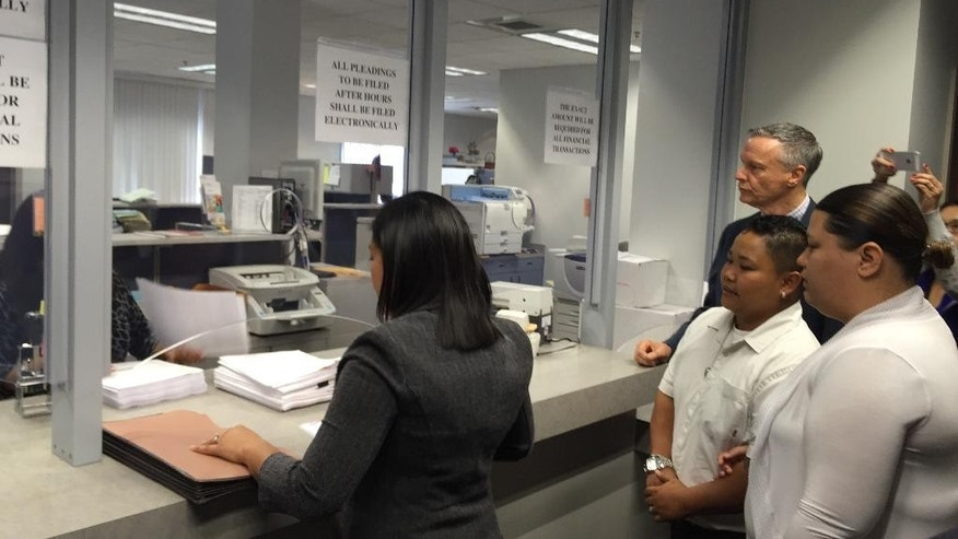 Sureta San Nicolas, file clerk for Thompson, Gutierrez, and Alcantara, files motions with the U.S. District Court in Guam on behalf of plaintiffs Kathleen M. Aguero and Loretta M. Pangelinan on Monday, April 13, 2015. The couple is seeking a federal court order to compel the Government of Guam Department of Public Health and Social Services to accept their marriage license application. Their attorney, Bill Pesch stands behind Pangelinan, left, and Aguero, right. (AP Photo/Grace Garces Bordallo)
