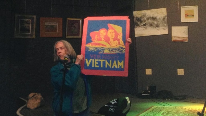 In this April 8, 2015 photo, Barbara Nolfi, who was part of the Franklin farming commune, holds up an artifact from the 1970s at a forum held by the Vermont Historical Society in Burlington, Vt. The state's population jumped 15 percent in the 1970s, with more than half of the increase coming from people moving from out of state to experimental communes in Vermont. The state historical society is doing a two-year research project on the era and its lasting influences in the state. (AP Photo/Lisa Rathke)