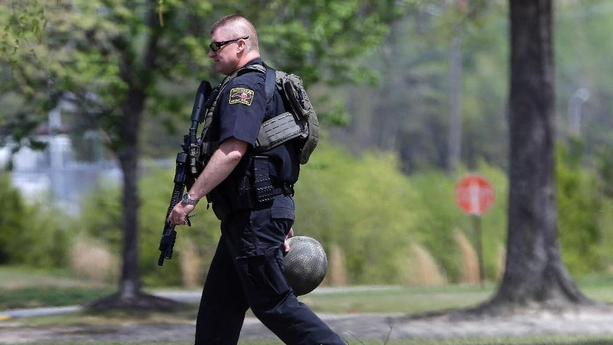 A North Carolina State Highway patrolman walks the grounds on campus following a shooting at Wayne Community College in Goldsboro, N.C., Monday, April 13, 2015. One person was killed and the campus was locked down as authorities searched for a gunman, officials said. (AP Photo/Gerry Broome)