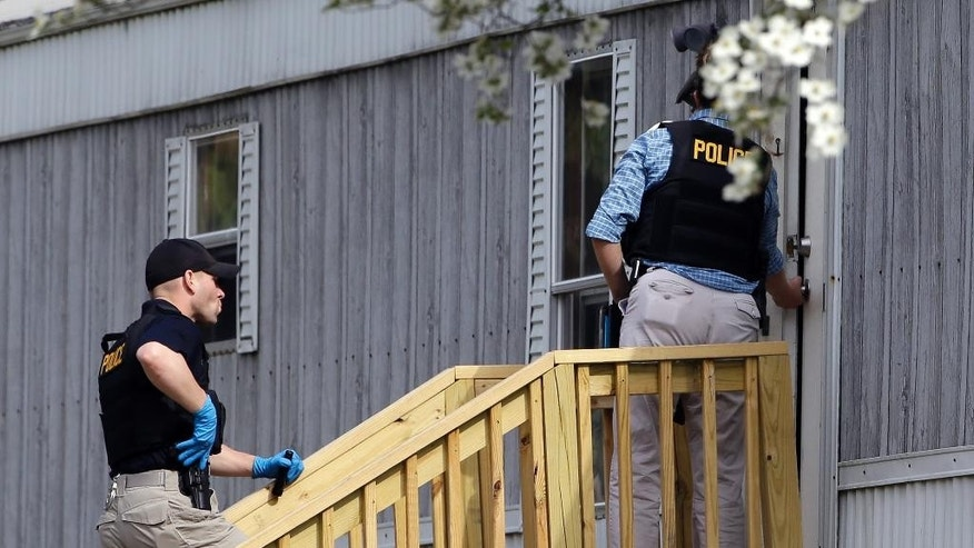 Authorities enter the home of shooting suspect Kenneth Stancil in Dudley, N.C., Monday, April 13, 2015 following a shooting at Wayne Community College. One person was killed Monday morning in a shooting at the community college that was locked down as authorities searched for the gunman, officials said. A manhunt is underway for Stancil. (AP Photo/Gerry Broome)