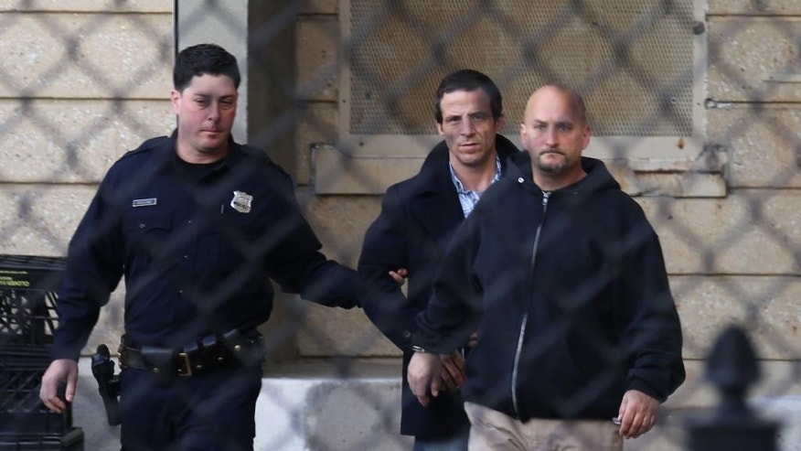Cardiologist Anthony Moschetto, right, 54, from the Long Island town of Sands Point, is escorted from the Nassau County police headquarters in Mineola, N.Y., Wednesday, April 15, 2015, after he and two other men were arrested on charges they took part in a killing-for-hire plot. The doctor is also accused of selling assault weapons and prescriptions for controlled substances. (AP Photo/Michael Balsamo)