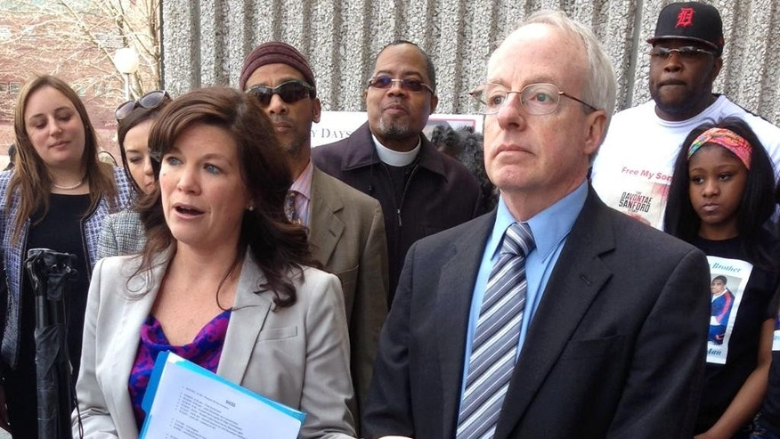 David Moran, right, of the Innocence Clinic at University of Michigan law school and Megan Crane, left, of the Center on Wrongful Convictions of Youth at Northwestern University law school,  speak to reporters Wednesday, April 15, 2015, outside the Wayne County courthouse in Detroit. They are asking a judge to throw out the murder convictions of Davontae Sanford, a young man who pleaded guilty in 2008 at age 15. A hit man, Vincent Smothers, has signed an affidavit taking responsibility for the murders. (AP Photo/Ed White)