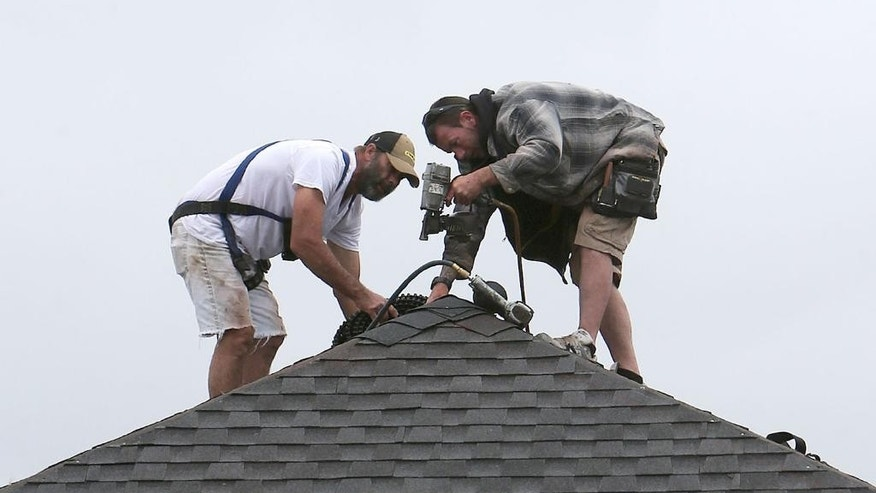 In this March 24, 2015 photo, roofers work on a new home in Panama City, Fla. The Federal Reserve releases its Beige Book report on Wednesday, April 15, 2015. (Andrew Wardlow/News Herald via AP)