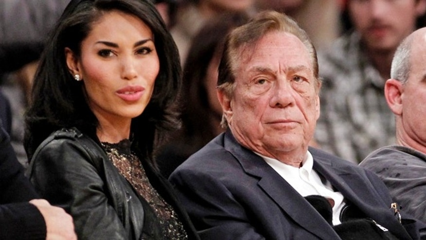 FILE - In this Dec. 19, 2011, file photo, Los Angeles Clippers owner Donald Sterling, right, sits with V. Stiviano as they watch the Clippers play the Los Angeles Lakers during an NBA basketball game in Los Angeles. (AP Photo/Danny Moloshok, File)