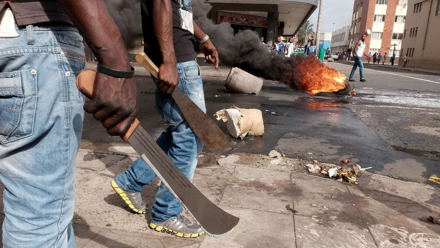 In this photo taken Tuesday, April 14, 2015, immigrant men armed with machetes make their way onto a Durban, South Africa, street during clashes with police and in search of locals that attacked foreign shop owners in the city center. (AP Photo/Tebogo Letsie)