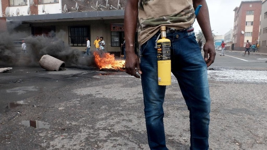 In this photo taken Tuesday, April 14, 2015, an immigrant armed with a petrol bomb on a Durban, South Africa, street during clashes with police and in search of locals that attacked foreign shop owners in the city center. (AP Photo/Tebogo Letsie)