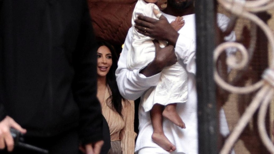 Kim Kardashian, a US reality TV star, and her husband Kanye West holding their daughter North West, walk inside Armenian St. James Cathedral, in Jerusalem, Monday, April 13, 2015. Kim Kardashian, along with husband West, their daughter, North West, and her sister, Khloe, arrived to Israel on a private visit.  (AP Photo/Mahmoud Illean)