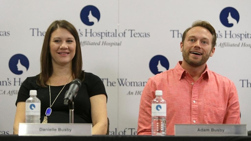 Parents Danielle Busby, left, and Adam Busby speak to the media at The Woman's Hospital of Texas, Wednesday, April 15, 2015, in Houston, about the birth of their quintuplet daughters. What is believed to be the first all-girl quintuplets born in the United States, were delivered by cesarean section on April 8.  (Melissa Phillip /Houston Chronicle via AP)