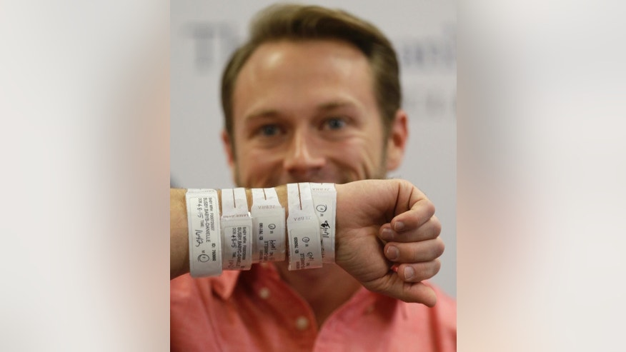Adam Busby displays his five hospital ID bracelets while he and his wife, Danielle Busby, speak to the media at The Woman's Hospital of Texas, Wednesday, April 15, 2015, in Houston, about the birth of their quintuplet daughters. What is believed to be the first all-girl quintuplets born in the United States, were delivered by cesarean section on April 8.  (Melissa Phillip /Houston Chronicle via AP)