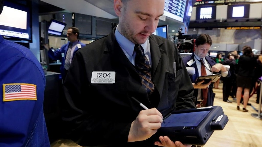 Trader Jonathan Wisniewski, center, works on the floor of the New York Stock Exchange Thursday, April 16, 2015. U.S. stocks are heading lower as more big companies turn in earnings.  (AP Photo/Richard Drew)