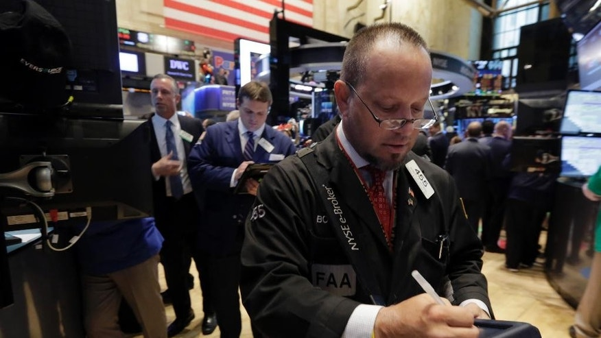 Trader Robert Arciero, right, works on the floor of the New York Stock Exchange Thursday, April 16, 2015. U.S. stocks are heading lower as more big companies turn in earnings.  (AP Photo/Richard Drew)