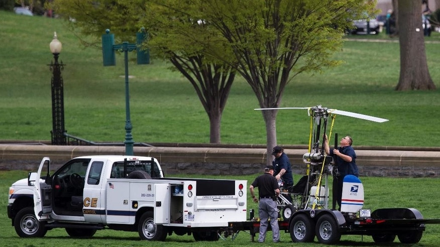 Capitol Police officers load a small helicopter onto a trailer, after a man landed on the West Lawn of the Capitol in Washington, Wednesday, April 15, 2015. Police arrested a man who steered his tiny, one-person helicopter onto the West Lawn of the U.S. Capitol Wednesday, astonishing spring tourists and prompting a temporary lockdown of the Capitol Visitor Center. Capitol Police didn't immediately identify the pilot or comment on his motive, but a Florida postal carrier named Doug Hughes took responsibility for the stunt on a website where he said he was delivering letters to all 535 members of Congress in order to draw attention to campaign finance corruption.   (AP Photo/Manuel Balce Ceneta)