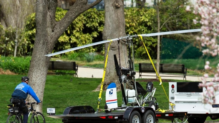 A Capitol Police officer on bike, follows a small helicopter loaded on a Capitol Police trailer, after a man landed on the West Lawn of the Capitol in Washington, Wednesday, April 15, 2015. Police arrested a man who steered his tiny, one-person helicopter onto the West Lawn of the U.S. Capitol Wednesday, astonishing spring tourists and prompting a temporary lockdown of the Capitol Visitor Center. Capitol Police didn't immediately identify the pilot or comment on his motive, but a Florida postal carrier named Doug Hughes took responsibility for the stunt on a website where he said he was delivering letters to all 535 members of Congress in order to draw attention to campaign finance corruption.   (AP Photo/Manuel Balce Ceneta)