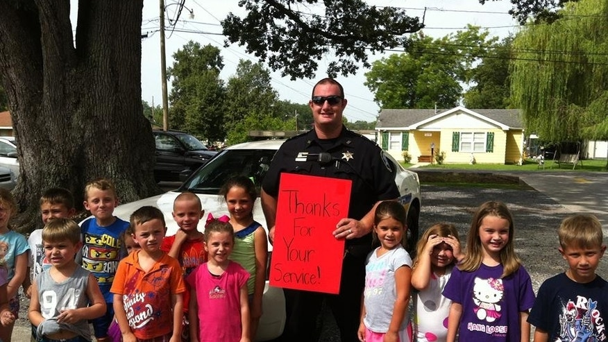 This undated photo released by the St. Charles Parish Sheriff's Office shows Cpl. Burt Hazeltine posing for a photograph with school children, in La. The 36-year-old Louisiana sheriff's deputy was directing traffic in a school zone Thursday morning, April 16, 2015, when he was shot three times by a man whose motive remains a mystery, authorities said. (St. Charles Parish Sheriff's Office via AP)