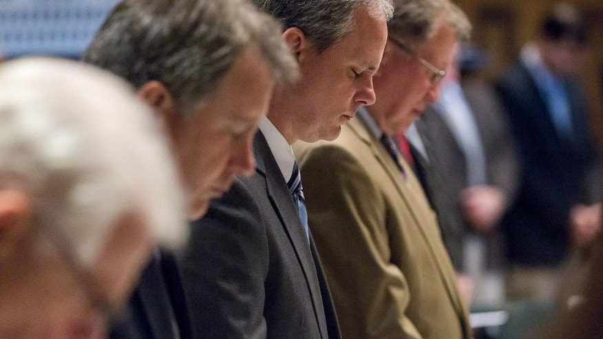 State Sen. John Stevens, R-Huntingdon, third from lefet, and other senators bow their heads during the prayer before the Senate floor session in Nashville, Tenn., on Thursday, April 16, 2015. State lawmakers were grappling over constitutional and theological concerns over a bill seeking to make the holy Bible the official book of Tennessee. (AP Photo/Erik Schelzig)