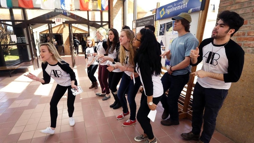 In a photo from Friday, April 10, 2015, Grace Kendall, left, sings with The Amazin' Blue, a A Cappella group, during a practice session at Pierpont commons in Ann Arbor, Mich. (AP Photo/Carlos Osorio)
