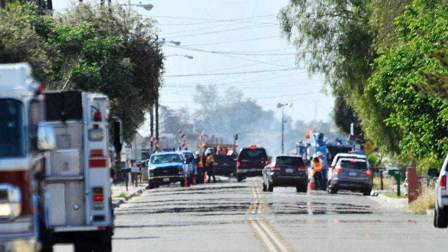 Pacific Gas & Electric crews are seen in the distance along N. Weber Avenue after a gas line was ruptured on Friday, April 17, 2015, in Fresno, Calif. The gas explosion closed both directions of a major highway in Central California and injured at least 15 people, four of them critically, authorities said Friday. (Eric Paul Zamora/The Fresno Bee via AP)