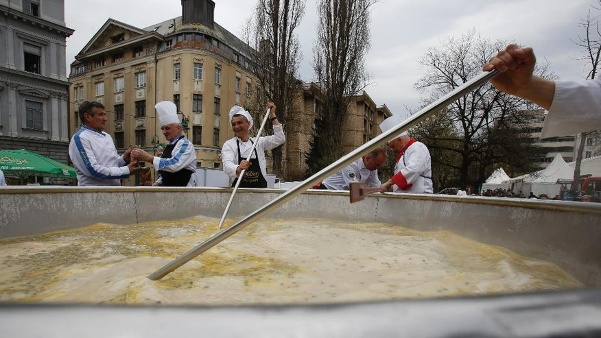 Bosnian cooks and volunteers prepare a chicken stew in Sarajevo, on Friday April 17, 2015. Bosnian chefs hope they have broken a Guinness record for the biggest chicken stew in the world, cooking up a meal for 14,000 people. The pot was set up in the center of Sarajevo and once the cooking was over the food was served to hundreds of people who gathered to watch the spectacle. (AP Photo/Amel Emric)