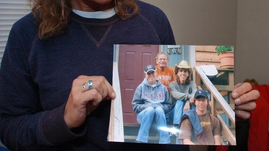 FILE - In this Nov. 5, 2013 file photo, Rhonda Whited-Rupp holds a picture of her sister, Sherry Arnold, seen in a cowboy hat, and Arnold's family in Sidney, Mont. Michael Keith Spell is scheduled to be sentenced Friday, April 17, 2015, convicted of the murder of Arnold, a Montana teacher whose death highlighted the downsides of an oil boom that's brought thousands of newcomers to the Northern Plains. Prosecutors are recommending 100 years in prison for Spell, 25, of Parachute, Colo., in the 2012 killing. Defense attorneys want Spell sentenced to an institution for the mentally disabled.(AP Photo/Matthew Brown, File)