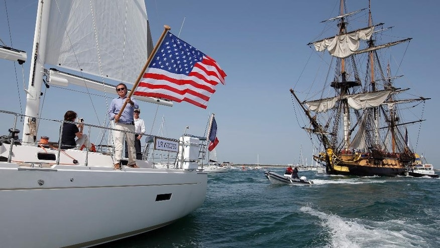 U.S sailing enthusiast from Newport, waves a flag as the frigate Hermione sails at La Rochelle, southwest France, as part of preparation of a trip to America, Wednesday, April 15, 2015. The replica of the frigate Hermione, which, in 1780, allowed La Fayette to cross the Atlantic to America and join the American rebels in their struggle for independence aims to cross the Atlantic and will sets off on Saturday. (AP Photo/Francois Mori)