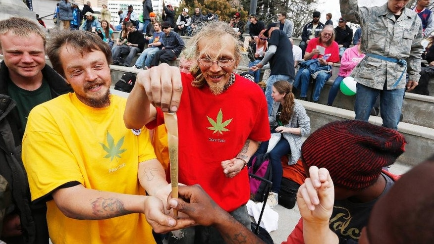 Partygoers prepare an oversized joint from pot donated by members of the crowd on one of several days of the annual 4/20 marijuana festival, in Denver's downtown Civic Center Park, Saturday April 18, 2015. The annual event is the second 4/20 marijuana celebration since retail marijuana stores began selling in January 2014. (AP Photo/Brennan Linsley)